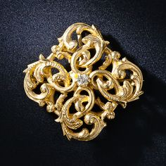 A single diamond sparkles from the center of sinuous interweaving scrolls, rendered in gleaming 14 karat gold, in this opulent adornment in the turn-of-the-twentieth century style.