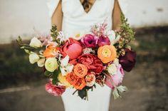 peony and ranunculus orange yellow pink warm hued bouquet