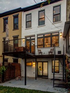 A new rear facade with enlarged doors and windows adds life and increases the living space of this traditional Brooklyn brownstone home. A new deck off the second story provides a spot for outdoor dining while offering cover for the patio below.