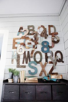 An assortment of wooden letters and numbers makes a provocative piece of wall art in the bunk room. The industrial bin below contains more than a dozen cubbies for storing toys.