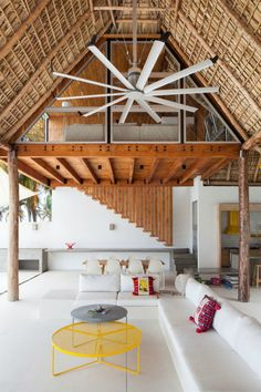 I am loving this stunning summer home with touches of sunny yellow! Traditional features such as wooden beams and roof made of of palm leaves have been combined with modern, straight lines and a minim