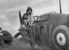 Sergeant B Furst of No. 310 (Czechoslovak) Squadron RAF is greeted by the squadron mascot on returning to Duxford, Cambridgeshire, after a sortie in his Hawker Hurricane Mark I.