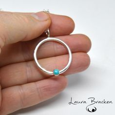 Simplicity involves unburdening your life. (Linda Breen Pierce)  Hand-fabricated pendant of sterling silver with a lovely 4mm Turquoise set in a 14k layered gold bezel.  This minimalist design is one of my signature pieces and will look great with just about any style of attire.  The circle is about 27mm in diameter (a smidge over an inch...