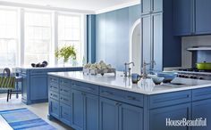 A brilliant shade of blue for cabinets, Sherwin-Williams's Searching Blue, brings excitement to a new kitchen with a traditional look.