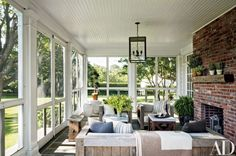 At the Hamptons retreat of AD contributing editor Rebecca Bond and her husband, Jon, the screened porch includes an Intérieurs lantern as well as stone-top tables and ceramic stools from Mecox; the striped pillows are made of a Loro Piana fabric   archdigest.com
