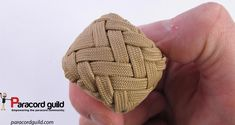 The knot tighten around a wooden sphere.