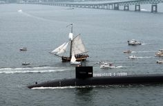 One of the Tall Ships passing under the Newport Bridge flanked by a submarine.