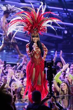 Carnival Nicki Minaj from the VMAs!  You'll need: - bright red sparkly leotard - headpiece/crown - long strips of red fabric - an infinite amount of feathers