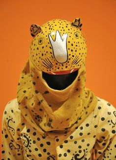 This image shows a typical wooden jaguar (tigre) mask from Suchiapa, Chiapas sewn to the cloth headdress with which the mask is worn. From the Ruth Lechuga mask collection exhibited at the Mexican Cultural Institute in Washington, DC