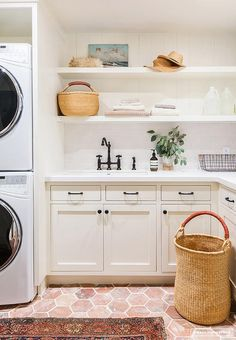 Red brick hex floors provide a pop of color to this white laundry room equipped with an enclosed stacked white front loading washer and dryer.
