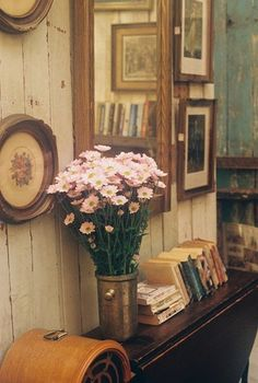 A rustic cabin gets a little feminine touch when rough and distressed wood walls and cabinetry come together with a bouquet of flowers and framed embroidery.