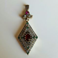 Vintage ruby and emerald diamond shaped pendent This beautiful vintage necklace pendent is diamond shaped! The lovely design includes red rubies, green emeralds and sparkling clear topaz natual gem stones. The siamond shape is centered with a red ruby and has rows of topaz and emerapd surrounding it. Two leaves and a ruby at the top easily fit any chain, metal is stamped 925 Sterling Silver and is 1.75 inches long.  Very lovely and unique accessory that can be added to your favorite outfit…