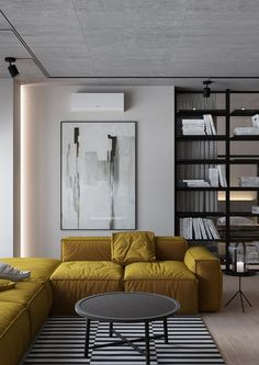 Yellow sectional sofa over black and white striped rug with tall book case in the background and abstract art