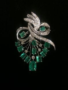 An emerald, diamond and fourteen karat white gold brooch  ribbon and spray motif set with step-cut emeralds and accented with single and baguette-cut diamonds; total diamond weight approximately: 2.00 carats.