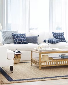 Start with a bright white sofa and add navy patterned pillows and rattan accents to create your coastal casual hideaway | #serenandlily