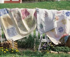 Antique quilts airing on a picket fence.