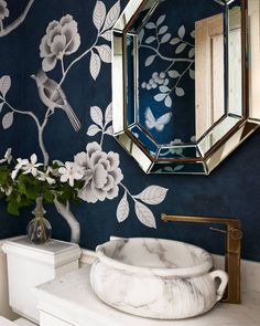 Bathroom Decorating Ideas. The prettiest powder room. | Photo: Bjorn Wallander, Interior Design: Alessandra Branca. White flowers stand in contrast to the navy blue wallpaper in this Chicago townhouse bathroom. The sink is by Michael S. Smith for Kallista, the fittings are by Dornbracht, the vintage mirror is by Bernd Goeckler Antiques and the wallpaper is from Fromental.