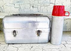 Priscilla Ware Aluminum Lunch Box and Thermos 2284 Vacuum Bottle, Industrial Lunch Box with Thermos, Both Included Lunch box Measures 12 long, 5 wide and 7 tall approximately. Thermos bottle is about 10 Tall and 3 diameter. A rustic, industrial style lunch box, made of aluminum, made by Priscilla Ware. Their motto, Speaks For Itself. Hinges intact and latches in fine working order. Coming with this wonderful collectible, is a Thermos Brand vacuum bottle. Made by The American Thermos…