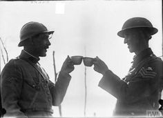 A French and British soldier toasting each other with ration wine during WWI, 1917