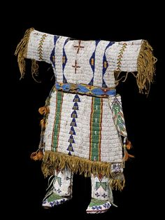 Sicangu Lakota (Sioux) girl's dress, ca. 1890, moccasins, ca. 1900, and leggings, ca. 1895. Hide, seedbeads, tin cones, sinew.