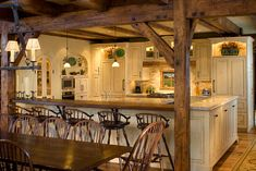 Kitchen - rustic beams combined unexpectedly with more sophisticated whitewashed cabinets  (Source: Timber Frame Kitchen - Denver - Robert Hawkins)