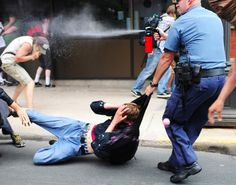 A police officer carrying a young man away, while spraying the spectators with pepper spray. AMERICA!