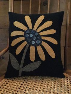 This is a great primitive penny rug pillow which is handmade by me. The pillow measures 11 by 13 inches. The front and back is black wool. The design features a mustard yellow flower with charcoal gr