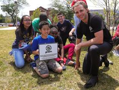 Patrick Kane takes a photo with a student after planting trees in Chicago as part of the NHL Green Legacy Tree Project.