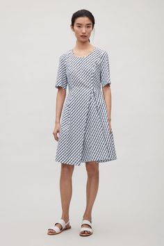 Coming in at the waist and flaring into a pleated skirt, this dress is made from a crisp cotton-mix with a slight stretch. It is completed with a round neckline, simple in-seam pockets a hidden zip fastening on the back.