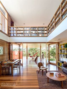 """Montada com pranchas de jequitibá, a estante de 1,15 m de altura faz as vezes de guarda-corpo. """"Em vez de esconder os volumes, optamos por deixá-los bem à vista, o que convida e incentiva as crianças a ler"""", conta o arquiteto Fabiano Sobreira."""