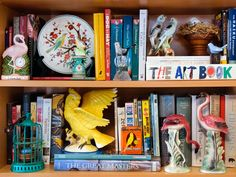 display collections with books... 'The different sizes, shapes and colors play off each other, and grouping a collection together gives it emphasis.' Gather up your treasures around the house and mass them for a stunning display.