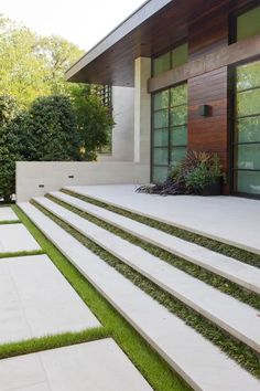 Facade of a Modern Home Featuring Floating Concrete Stairs Separated By Grass Strips