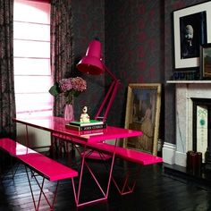 vivid pink table, dark walls and floor