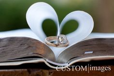 The wedding rings on a family bible with the pages folded like a heart shape.