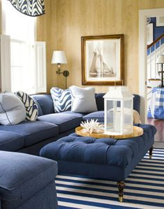 Brown and White Themed Navy Living Room Ideas with Cool Blue Fabric Sofa Furniture that have Retro Style Pillow Accessories and Comfortable Soft Rectangle Shaped Table on the Line Pattern Rugs also Beautiful Picture Frame Wall Accessories Decorating