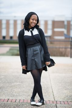 Deshaune is a student at St. Augustines University in Raleigh, NC. Shes wearing a monochromatic outfit. Black Cardigan, contrast white and black shirt over a high waist black skirt, a black leather bag and black and white saddle shoes