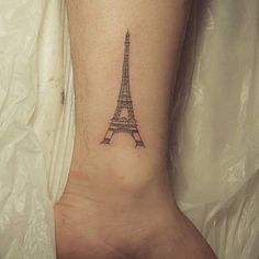 Fine line style eiffel tower tattoo on the ankle. Tattoo artist:...