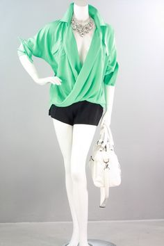 This front twist wrap shirt looks perfect paired with a high-waist skirt, skinnies or shorts with ankle boots! It features a surplice neckline with a spread collar, long sleeves with banded button cuffs and cut longer at the back for added style. The shirt is available in Spring Green (shown), Hot Pink and Black. Small, Medium, Large. 100% Polyester. $34.99