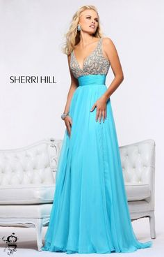 Love Nude but want Color too!?! Sherri Hill 1563 is the prom dress for you! This gown has a deep V neckline with two supportive shoulder straps. The upper bodice is embellished with lace like beading over a nude fabric. The flowing A line silky chiffon skirt is ideal for walking and posing all night long! A sexy deep V in the back also makes this dress a timeless style that we know you will love!