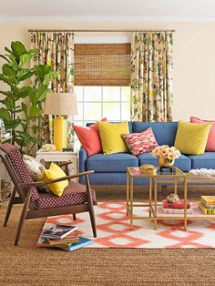 eclectic and colorful living room style | pops of coral, blue, and yellow + layered ikat and natural woven rugs + staked table books + gold accents + fig tree