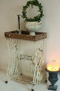 A sewing machine base topped with a rustic wooden tray serves as a side table in this rustic vignette.