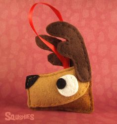 Comet is a felt reindeer Christmas ornament. A red ribbon makes him easy to hang on a Christmas tree or use as a gift topper. Comet is hand-cut and hand stitche