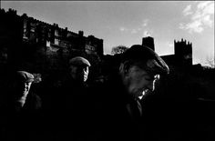 Ian Berry - GB. England. Durham. Three men in cloth caps, probably coal miners, with Durham Castle and cathedral in the background. 1974