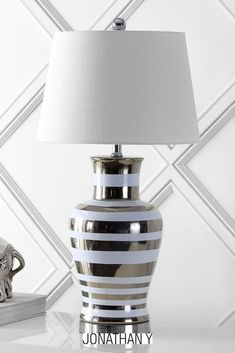 Our modern take on a classic lamp features silver stripes on a white ceramic base. Try a pair of these fresh, modern lamps in a bedroom, living room, or entry console. Add sparkle to a Hollywood Regency room; the drum shade suits modern interiors. Includes an energy-saving LED bulb. Table Lighting, Light Table, Unique Table Lamps, Modern Lamps, Build Your Dream Home, Modern Interiors, Fabric Shades, Hollywood Regency, Drum Shade