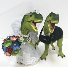 Custom dinosaur cake topper.   Pick your wedding colors for bouquet and bow tie. #dinosaurcaketopper #uniquecaketopper #weddingcaketopper #quirkycaketoppper #bestcaketopper