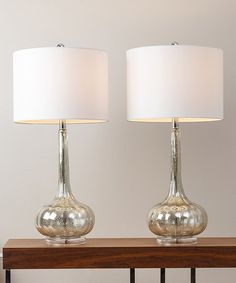 Created from shimmering silver mercury glass, these sleek lamps illuminate a space with elegance.