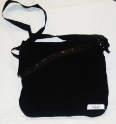 Sigfrid – Borsa a tracolla realizzata in tessuto nero in lana.  La borsa è' stata lavorata per ottenere rigidità  Il manico nero è regolabile ed è fissato tramite una fibbia di metallo alle asole della borsa. (etc.)  Realizzata interamente a mano. Modello unico.