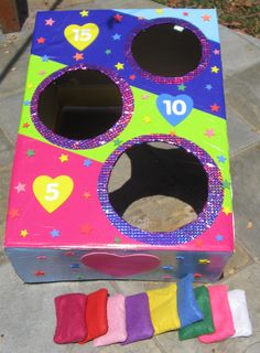 I made this bean bag toss game for thalia's rainbow party. For the game i used a large box, bright wrapping paper, glue, stickers and contact and for the bean bags I used bright coloured felt and rice :) it was a big hit