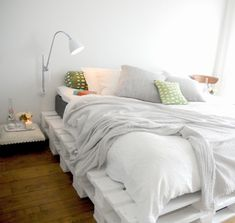 White pallet bed, gray and colored pillows, reading light, and a tool for a bedside table. <3