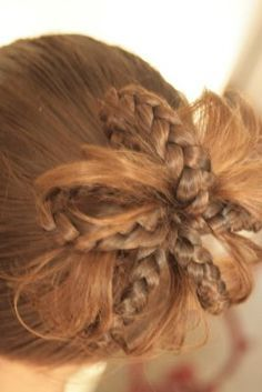 Make ponytail, make 5 braids in ponytail. Loop braid ends back through the band holding the ponytail. Done.